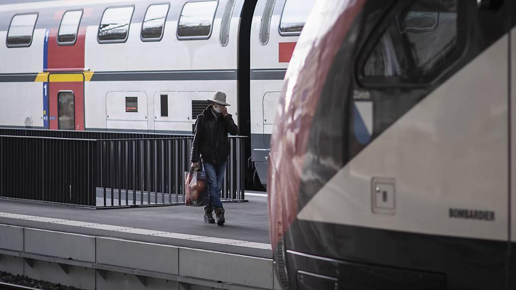 Ein Mann mit Maske auf dem Weg zum Zug am Bahnhof in St. Gallen. (Archivbild)
