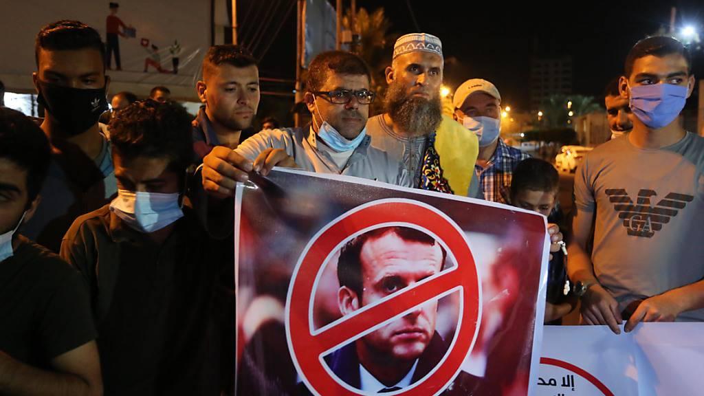 Ein Palästinenser hält bei einer Protestaktion ein Anti-Macron-Plakat. Foto: Ashraf Amra/APA Images via ZUMA Wire/dpa