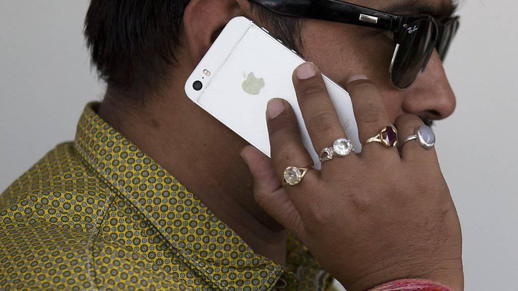 Ein Inder telefoniert mit einem iPhone. Aufgrund von Reformen der indischen Regierung kann Apple nun eigene Läden in Indien eröffnen. (Symbolbild)