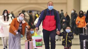 Reisende mit Gesichtsmasken im Bahnhof von Wuhan. Nach neusten Behördenangaben sind bisher neun Menschen wegen des neuen Virus gestorben.