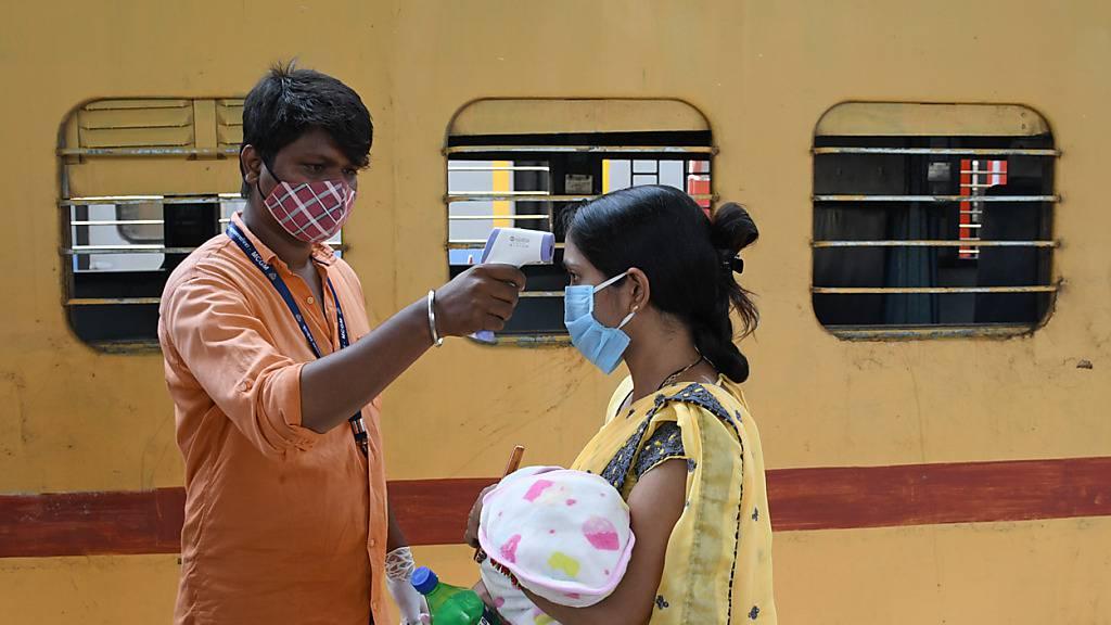 Ein Mitarbeiter misst die Temperatur bei einer Frau, die ein Baby auf dem Arm trägt, auf einem Bahnsteig im indischen Mumbai. Foto: Ashish Vaishnav/SOPA Images via ZUMA Wire/dpa