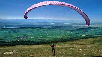 Ein Gleitschirmflieger startet im Jura zu einem Flug. (Symbolbild)