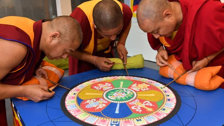 Die drei Mönche beim Streuen des Sandmandalas.