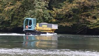 Schwer beladen: Das Raupenfahrzeug pflügt sich durchs Wasser.