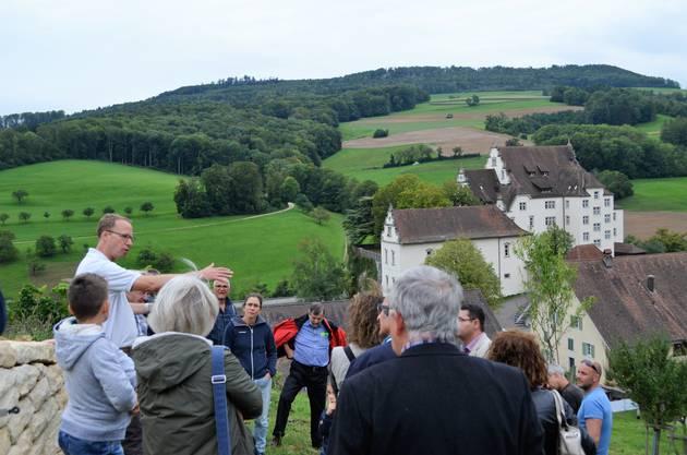 Die Sanierung der 400-jährigen Bruchsteinmauern beim Schloss Kasteln in Oberflachs ist demnächst abgeschlossen.Ulysses Witzig, (links, weisses Shirt), erläutert den Gästen die Bedeutung der Trockensteinmauern.
