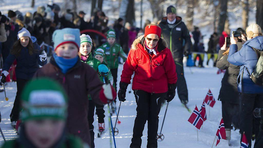 Die norwegische Königin Sonja gleitet gemeinsam mit vielen Kindern auf Langlaufskiern über den Schlossplatz, auf dem zum 25. Thronjubiläum eine riesige Wintersportlandschaft entstand.