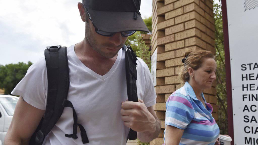 Bekleidet mit T-Shirt, Baseballmütze und Sonnenbrille betritt Oscar Pistorius die Polizeiwache in Garsfontein