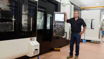 Reto Ziegler vor einer Multi-Funktions-Werkzeugmaschine, die im Erweiterungsbau steht.
