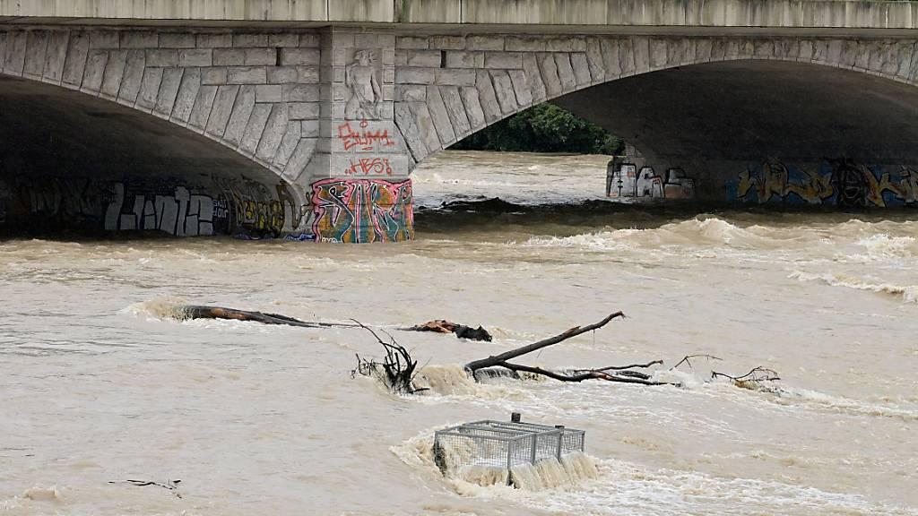 Braunes Wasser fließt nach starken Regenfällen unter der Reichenbachbrücke durch das Flussbett der Isar in München. Foto: Peter Kneffel/dpa
