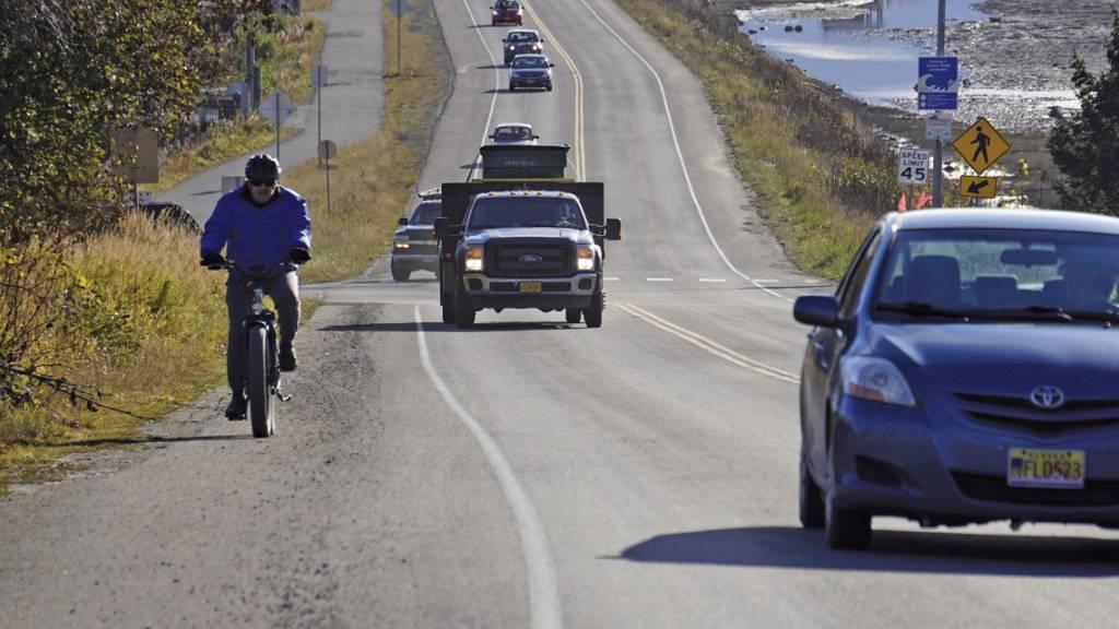 Ein Fahrradfahrer und mehrere Autos verlassen Homer, nachdem eine Tsunami-Evakuierung für tief gelegene Gebiete in Homer erlassen worden war. Ein Erdbeben hat die Küste des US-Bundesstaates Alaska erschüttert.