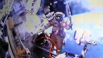 Der russische Kosmonaut Oleg Kotov hält die olympische Fackel für Sotschi ausserhalb der ISS-Raumstation. Zu sehen ist dies auf einem riesigen Bildschirm im Kontrollcenter.