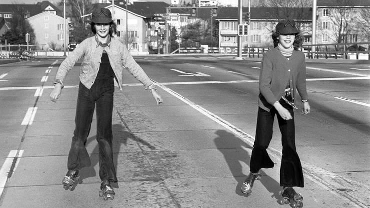 Zwei junge Mädchen geniessen  beim Rollschuhlaufen die leeren Strassen während einem autofreien Sonntag am 21. November 1973 in Zürich.