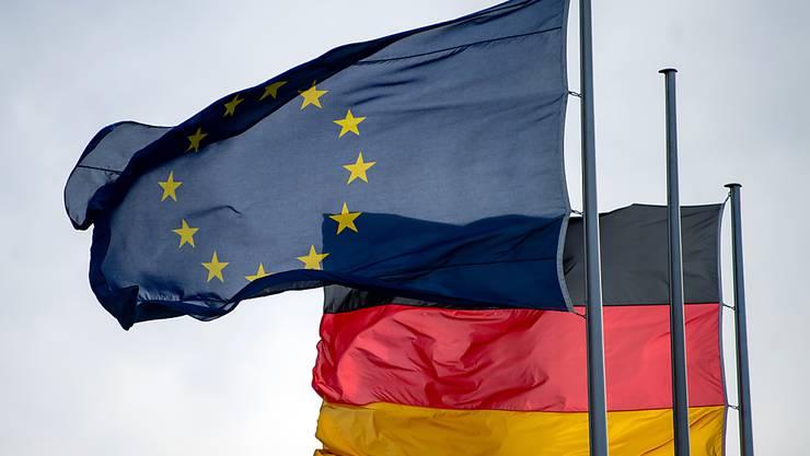 ARCHIV - Die Flaggen der Europäischen Union und der Bundesrepublik Deutschland wehen vor dem Reichstag im Wind. Foto: Monika Skolimowska/zb/dpa