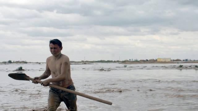 Ein Afghane watet durch das Hochwasser Schebergan