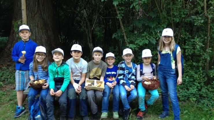 Stolze Jugendgruppe mit einer Auswahl der gefundenen Pilze