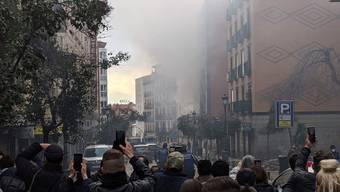 Rauch und Staub in Madrid. Passanten filmen den Vorgang mit ihren Handys.