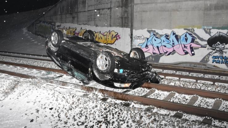 Nach einer Verfolgungsjagd mit der St. Galler Polizei landet der Wagen eines 20-jährigen Lenkers auf dem Dach liegend auf dem Bahngleis. (St. Galler Kantonspolizei)