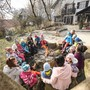 Kinder und Betreuerinnen singen am Lagerfeuer.