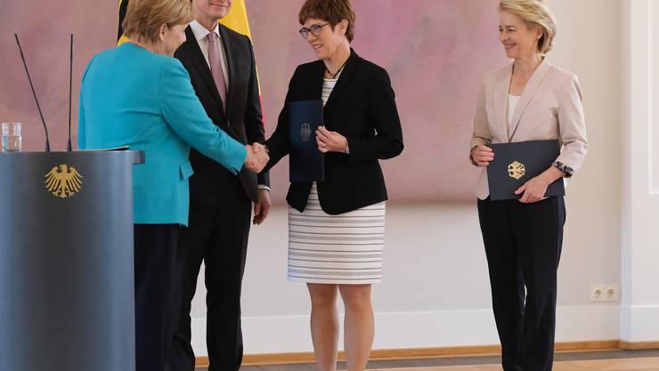 Angela Merkel gratuliert der neuen deutschen Verteidigungsministerin Annegret Kramp-Karrenbauer. Rechts ihre Vorgängerin, die frischgewählte EU-Kommissionspräsidentin Ursula von der Leyen.
