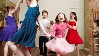 Körpersprache: Ausgelassen tanzende Kinder an einem Geburtstagsfest.