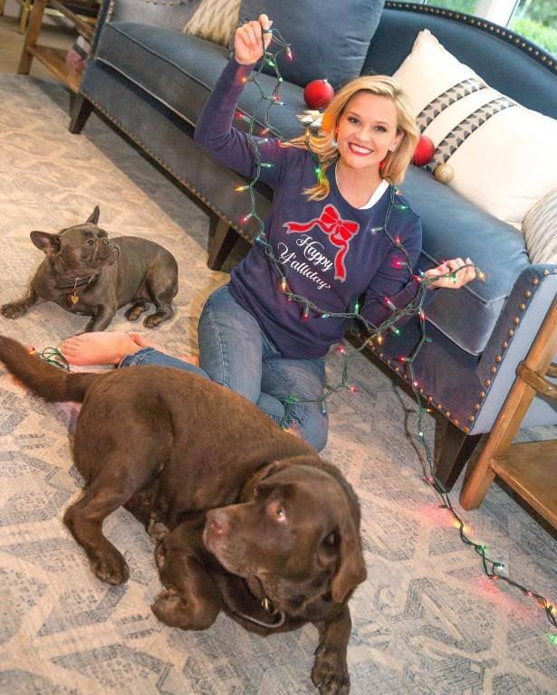 Schauspielerin Reese Witherspoon posiert mit Hunden und Lichterkette.