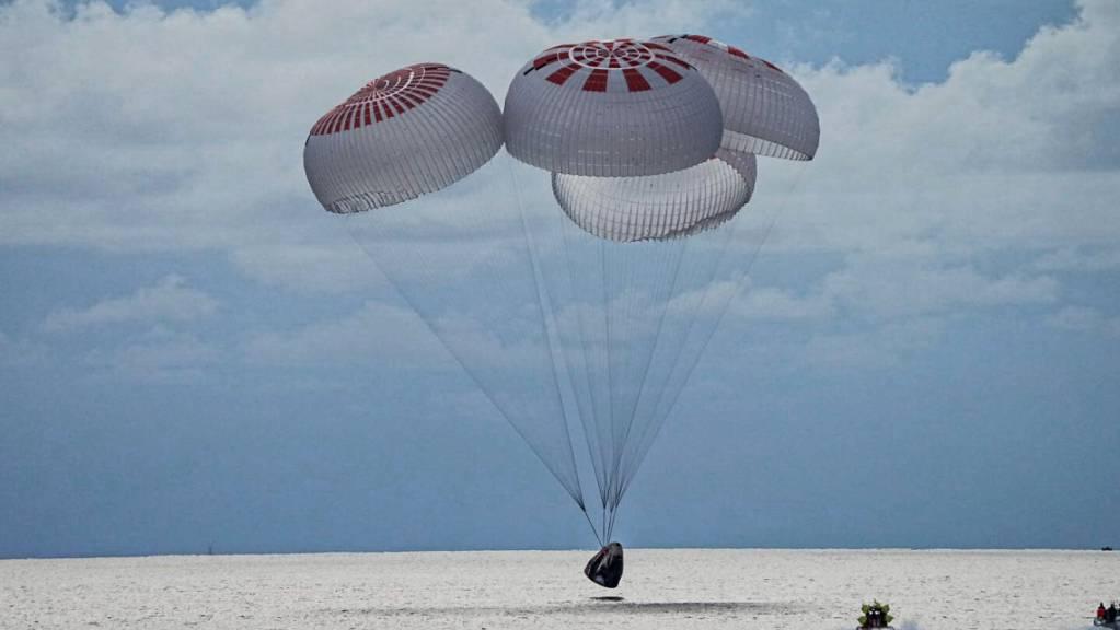 Eine SpaceX-Kapsel mit vier Personen an Bord geht vor der Küste Floridas mit Fallschirmen in den Atlantik nieder. Foto: Uncredited/SpaceX via AP/dpa - ACHTUNG: Nur zur redaktionellen Verwendung und nur mit vollständiger Nennung des vorstehenden Credits bis 14 Tage nach Sendedatum.