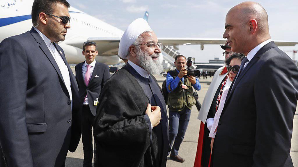 Bundespräsident Alain Berset (rechts) begrüsst seinen iranischen Amtskollegen Hassan Ruhani (Mitte) nach dessen Ankunft am Nachmittag in Zürich-Kloten.