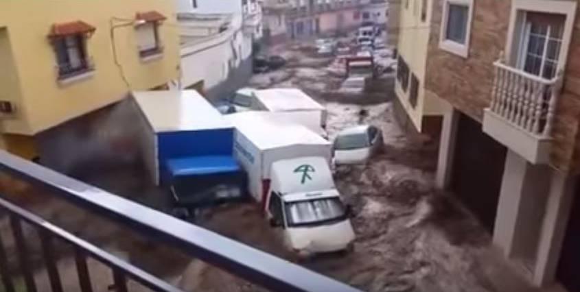 Von dem sicheren Balkon aus filmen Einwohner in Adra, wie das Wasser die Autos davonschwemmt.