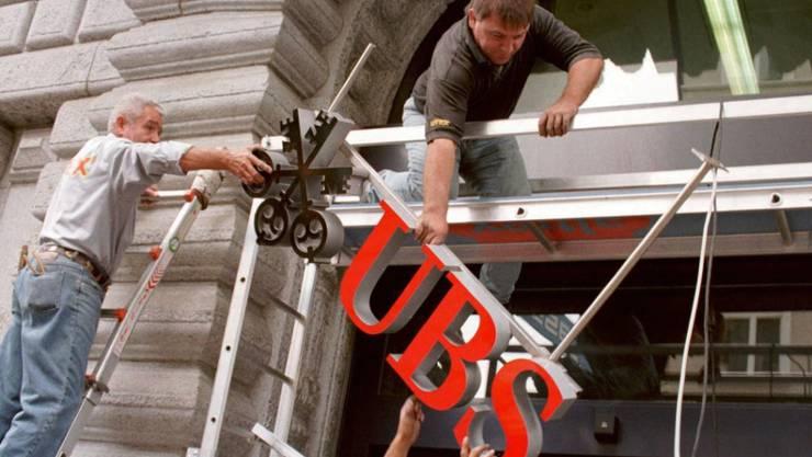 Handwerker hängen im Juni 1998 nach der genehmigten Fusion zwischen der früheren Schweizerischen Bankgesellschaft und des Schweizerischen Bankvereins die neuen UBS-Schilder auf. (Archiv)