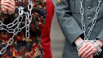 Gegen jeglichen Zwang: Mitglieder des Initiativkomitees inMilitärkleidung und Ketten während einer Aktion 2012 in Bern. KEYSTONE