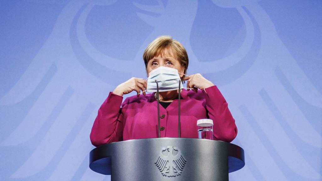 ARCHIV - Bundeskanzlerin Angela Merkel (CDU) setzt nach einem Pressestatement ihre Maske auf. Das Bundeskabinett hat die Änderung des Infektionsschutzgesetzes beschlossen. Foto: Michael Kappeler/dpa-pool/dpa