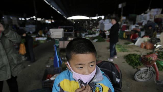 Ein Kind mit einem Mundschutz auf einem geschlossenen Geflügelmarkt in Huhuai (Archiv)
