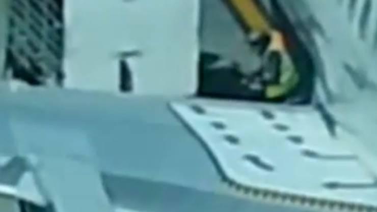 Hier durchwühlt ein Flughafen-Mitarbeiter den Koffer eines Reisenden.