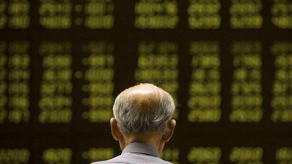 Ein chinesicher Anleger schaut in Peking auf ein Kurstableau: Die Kurse an den chinesischen Börsen sind am Dinestag erneut stark zurückgegangen.