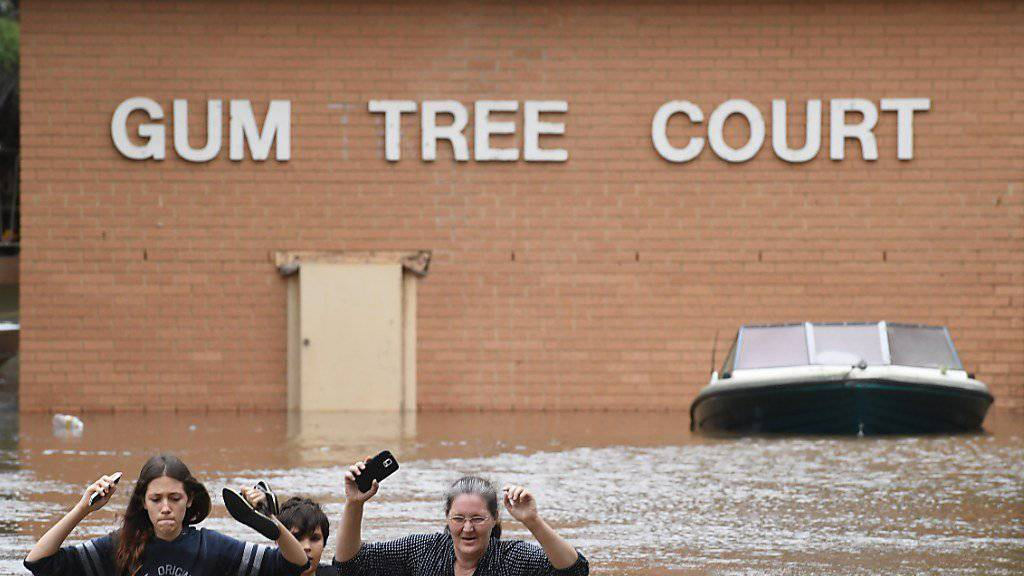 Einwohner der australischen Ortschaft Lismore waten durch das Wasser, das Zyklon Debbie der Region beschert hat.