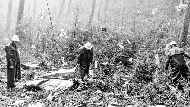 Feuerwehrleute und Polizisten an der Absturzstelle der Swissair-Coronado. Am 21. Februar 1970 explodierte – kurz nach dem Start – im Frachtraum eine Bombe, die von palästinensischen Terroristen gelegt worden war. Keystone