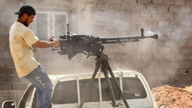 Ein Kämpfer der einstigen libyschen Rebellen schiesst bei einem Checkpoint um sich (Archiv)