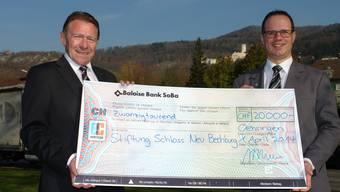 Stiftungspräsident Kurt Zimmerli (links) nimmt den Check von Adrian Bernasconi von der Baloise Bank SoBa entgegen.