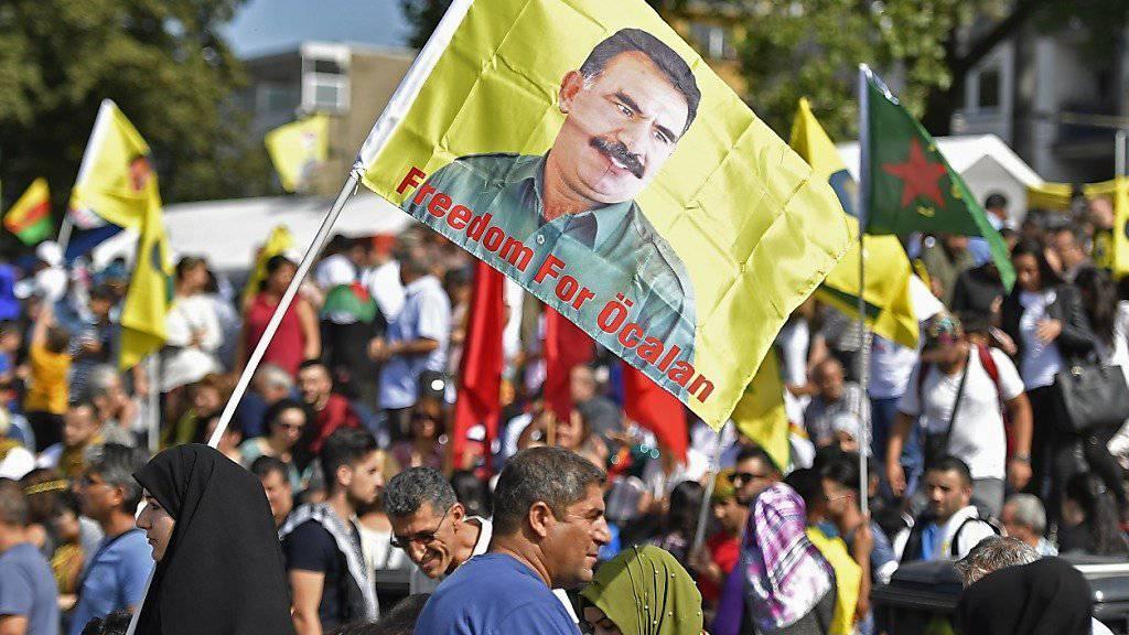 Eine Demonstrantin hält in Köln eine Öcalan-Flagge hoch.