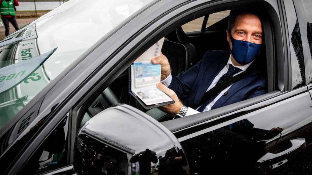 Gesundheitsminister Hugo de Jonge zeigt in einem Auto am Straßenrand den Medienvertretern seine ungültigen Reisepass. De Jonge ist am Mittwoch im ersten Anlauf bei der Abgabe seiner Stimme für die Parlamentswahl gescheitert. Foto: Jeffrey Groeneweg/ANP/dpa