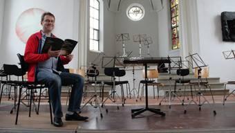 Martin Völlinger sitzt in der alten Kirche in Boswil. Seine Messe, die er in der Hand hält, wird am Sonntag in der Pfarrkirche von neun Chören aufgeführt.