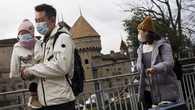 Asiatische Touristen mit Schutzmasken vor dem Chateau de Chillon.