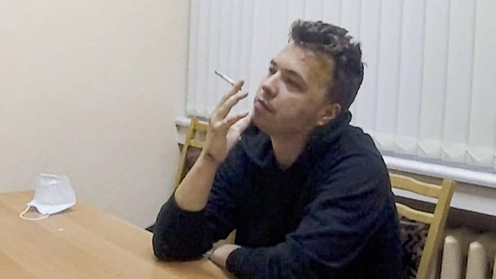 HANDOUT - Das vom belarussischen ONT-Kanal zur Verfügung gestellte Videostandbild zeigt den Aktivisten und Blogger Raman Pratasewitsch, der an einem Tisch sitzt und eine Zigarette raucht. In einem einstündigen Video, das auf dem staatlichen Sender ONT ausgestrahlt wurde, wird der Regimekritiker in einem Haftzentrum gezeigt. Foto: Uncredited/ONT channel/AP/dpa - ACHTUNG: Nur zur redaktionellen Verwendung im Zusammenhang mit der aktuellen Berichterstattung und nur mit vollständiger Nennung des vorstehenden Credits