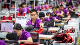 Chinesische Arbeiterinnen und Arbeiter in einer Fabrik für Kinderbekleidung.