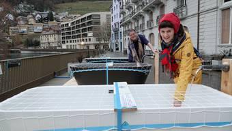 Kurze Auszeit: Kathrin Doppler vom Verein Bagni Popolari und ein Passant wärmen sich am Ufer der Limmat in den Wannen die Hände.