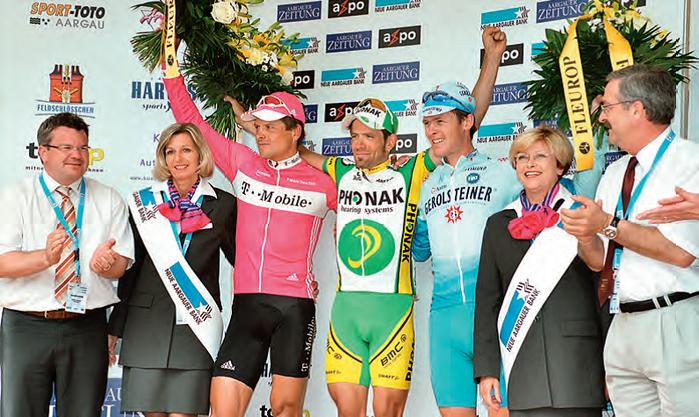OK-Präsident Marco Canonica (links) und Heinz Sager (rechts) von der NAB freuen  sich über den Schweizer Erfolg. Auf dem Podest von 2005 stehen Jan Ullrich (2.), Alexandre Moos (1.) und Marcel Stauss (3.).