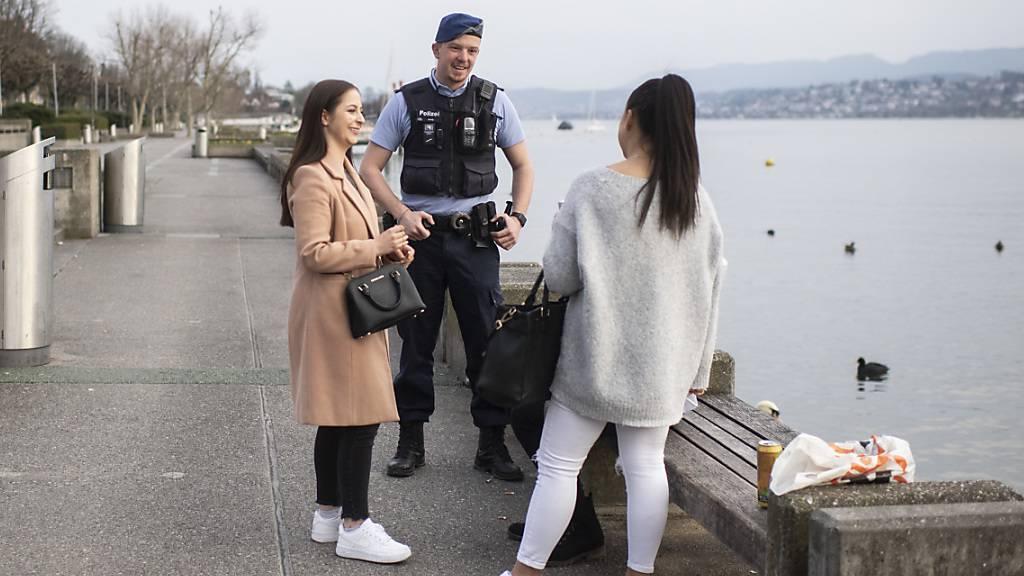 An der Seepromenade in Zürich: ein Polizist rät jungen Leuten, nach Hause zu gehen.
