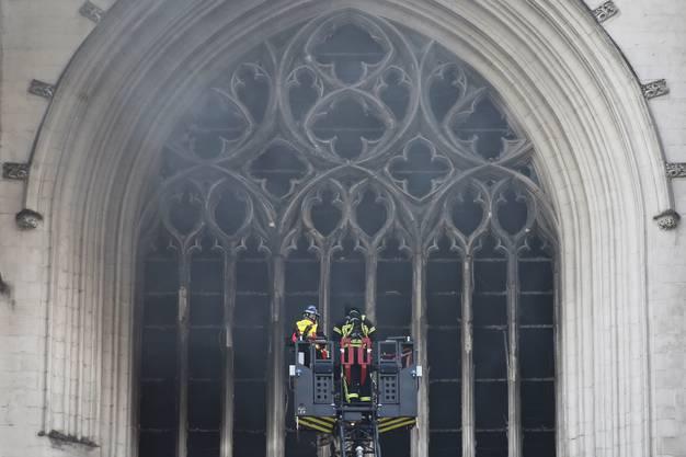 Zwei Feuerwehrleute bei den Löscharbeiten hoch oben an der gotischen Kathedrale von Nantes. (Bild: Keystone)