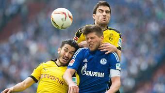 Schalkes Klaas-Jan Huntelaar (mitte) behauptet sich gleich gegen zwei Dortmunder (Nuri Sahin und Sokratis). Huntelaar erzielte nach 66 Minuten das Tor zum 2:2-Schlussstand