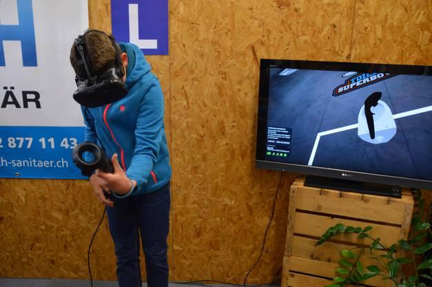 Ein junger Messebesucher versucht sich im virtuellen Kloschüssel-Weitwurf.